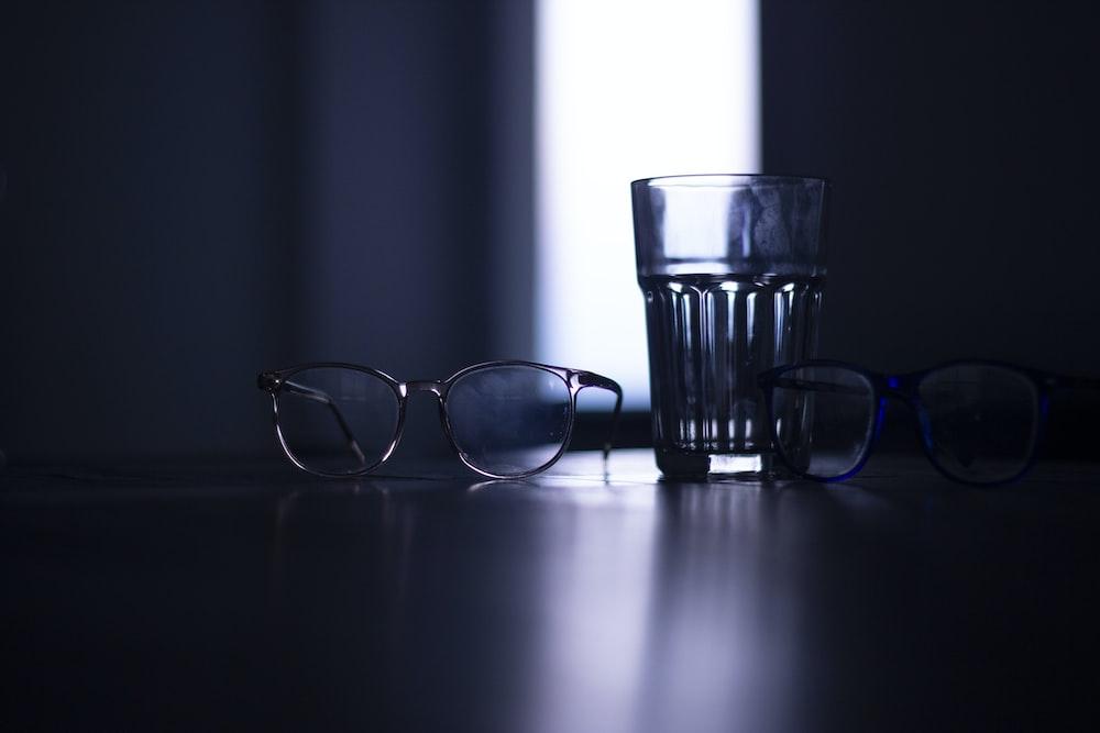 black framed eyeglasses beside clear drinking glass