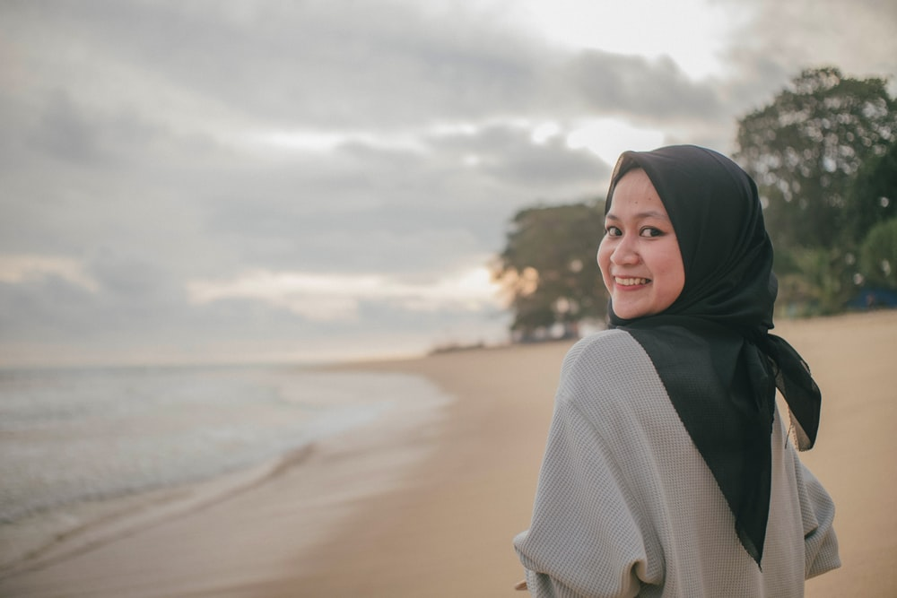 woman in white knit sweater and black hijab