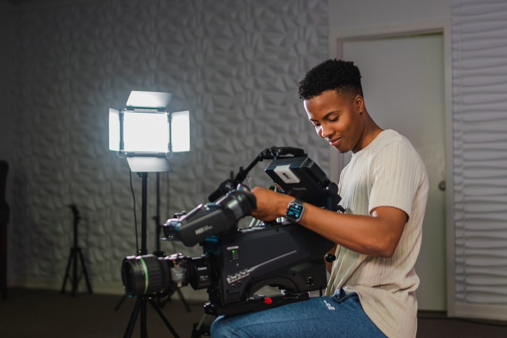 man in white t-shirt and blue denim jeans sitting on chair holding black dslr camera