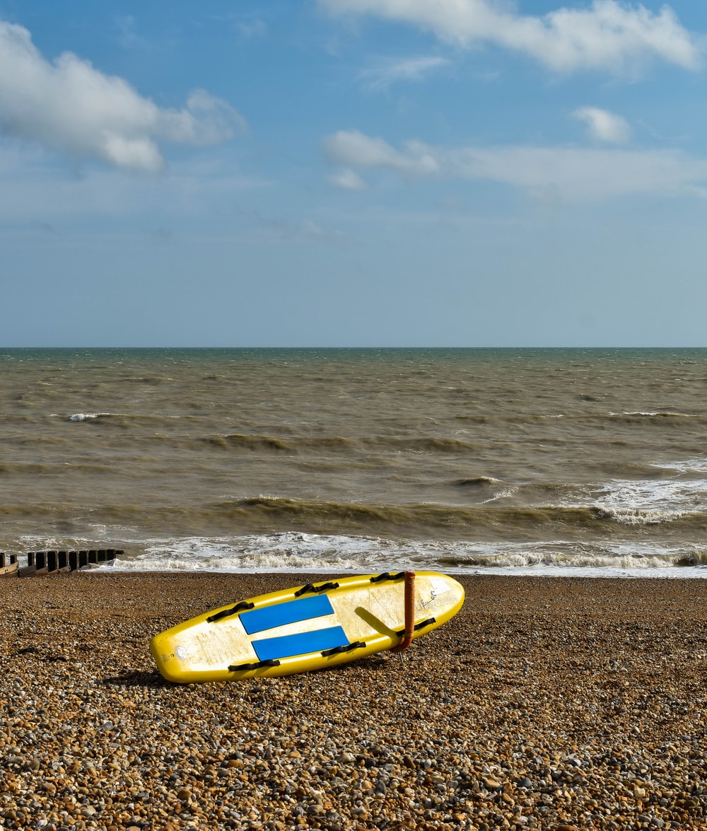 yellow and blue kayak on beach shore during daytime