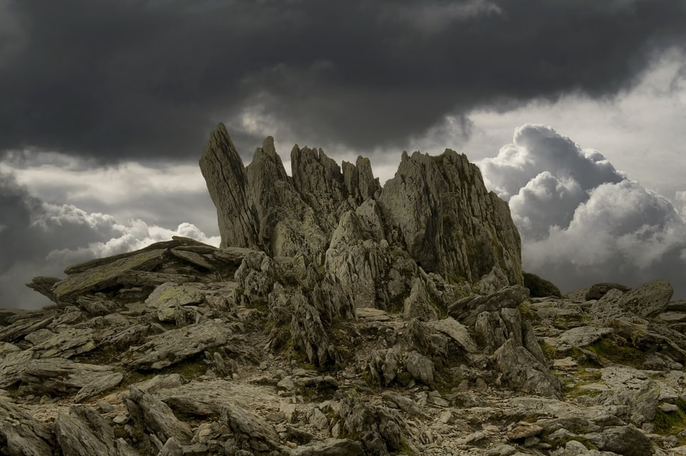 gray rocky mountain under cloudy sky during daytime
