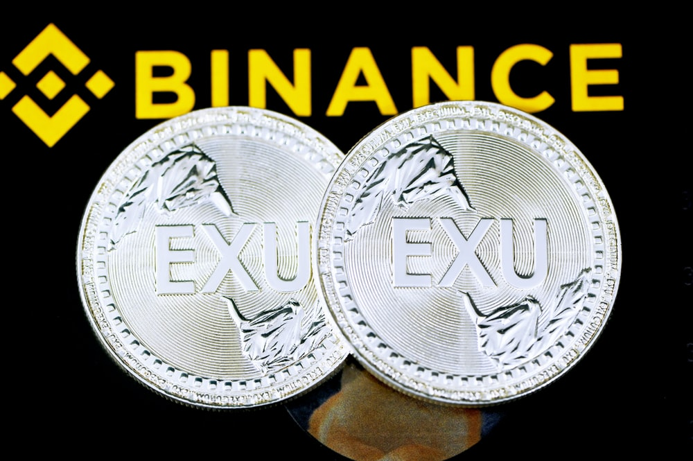 silver round coin on black and yellow textile