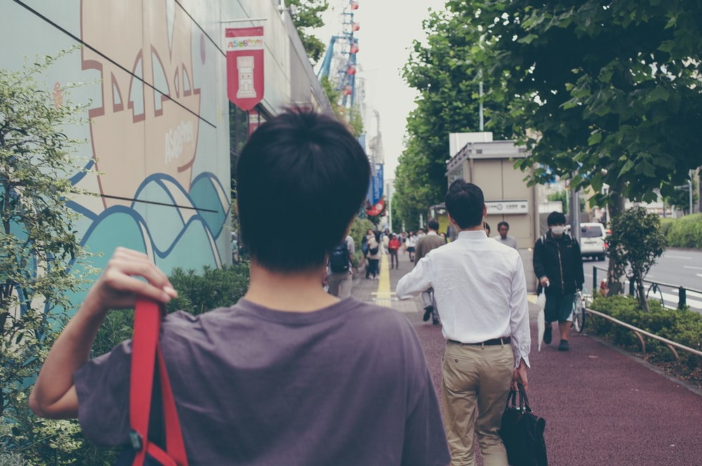 man in white crew neck t-shirt standing near people walking on street during daytime