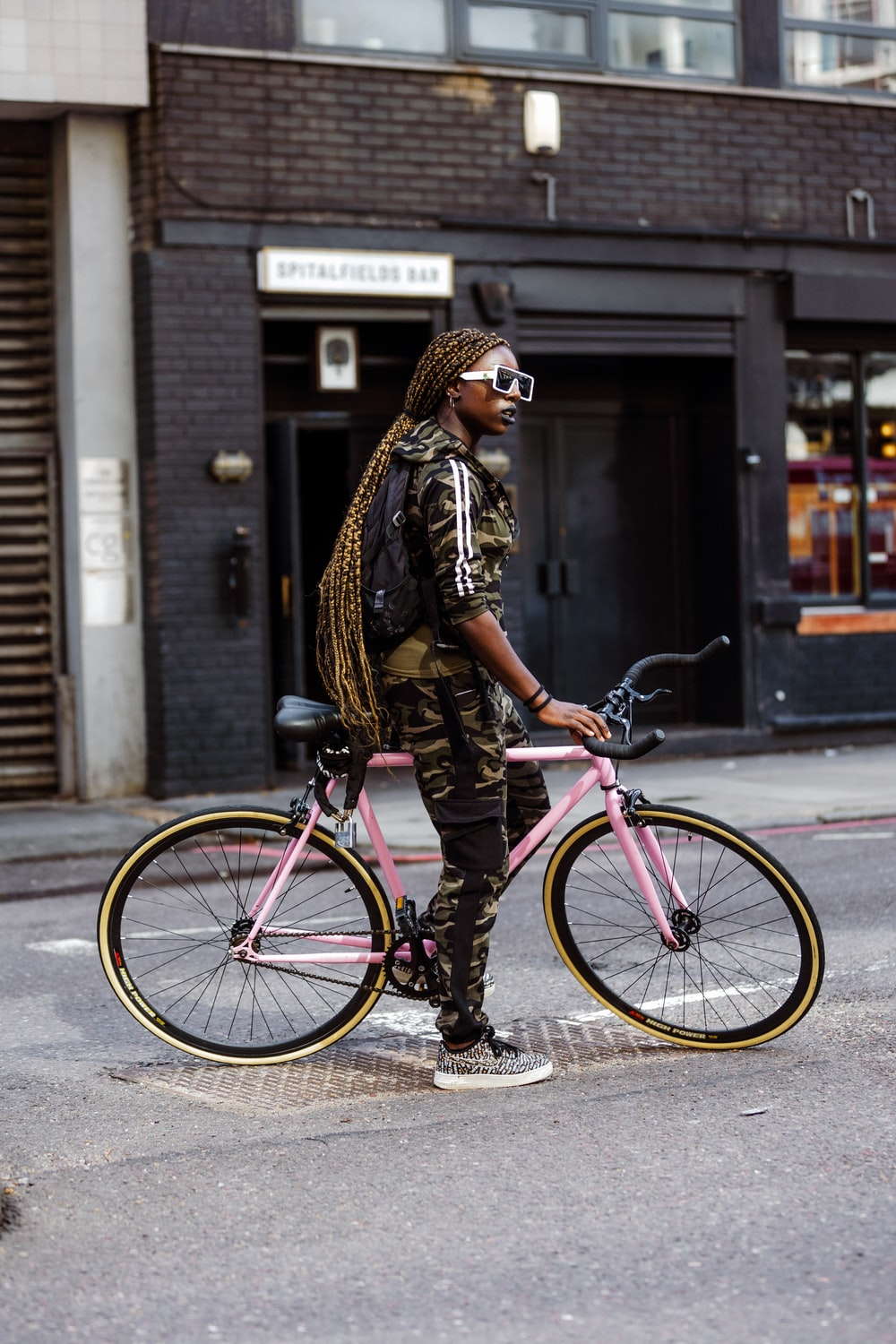 woman in brown and black leopard print jacket and black pants riding pink bicycle