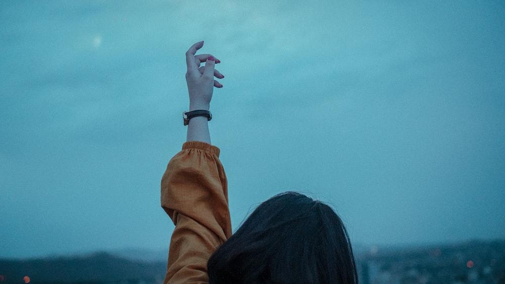 woman in brown jacket raising her left hand
