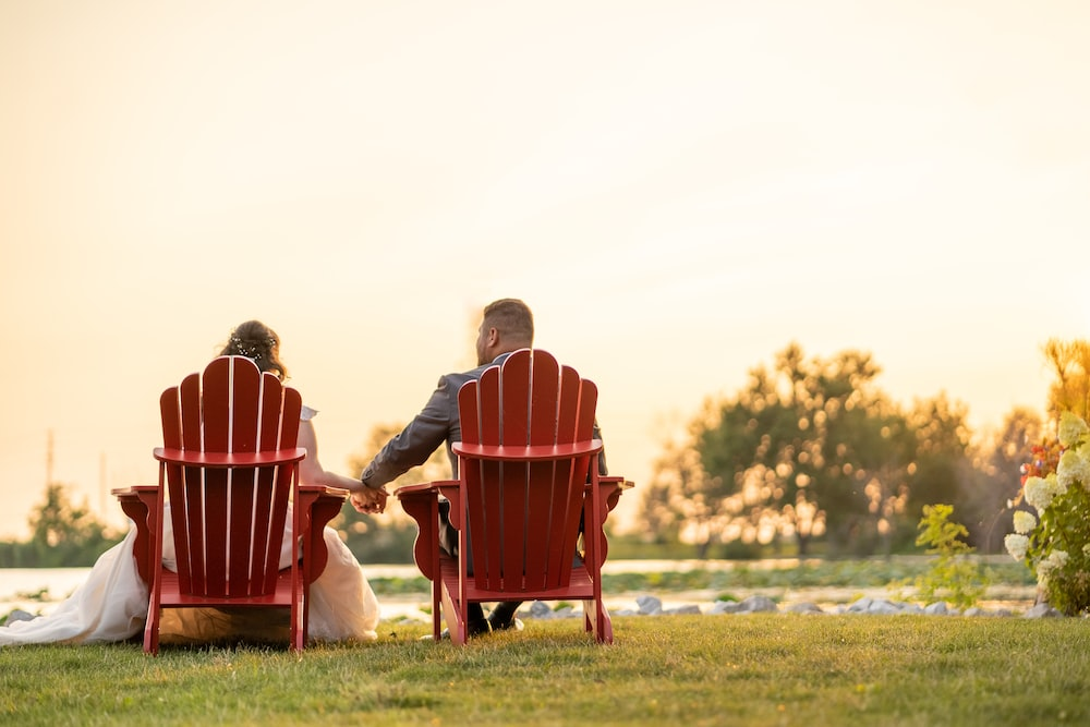 man and woman sitting on red chair on green grass field during daytime