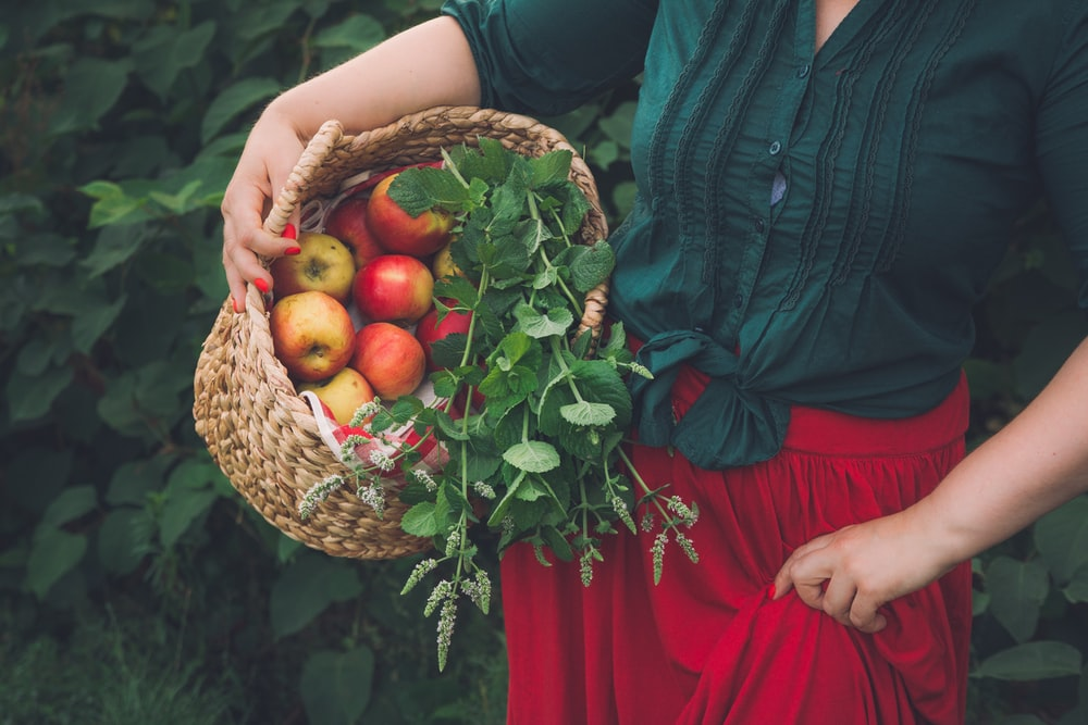 woman in red dress holding brown woven basket with red and yellow fruits