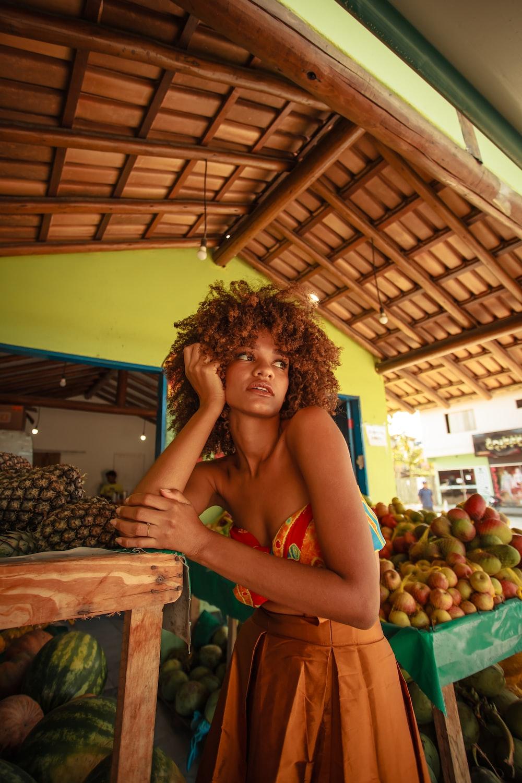 woman in red bikini standing near fruit stand