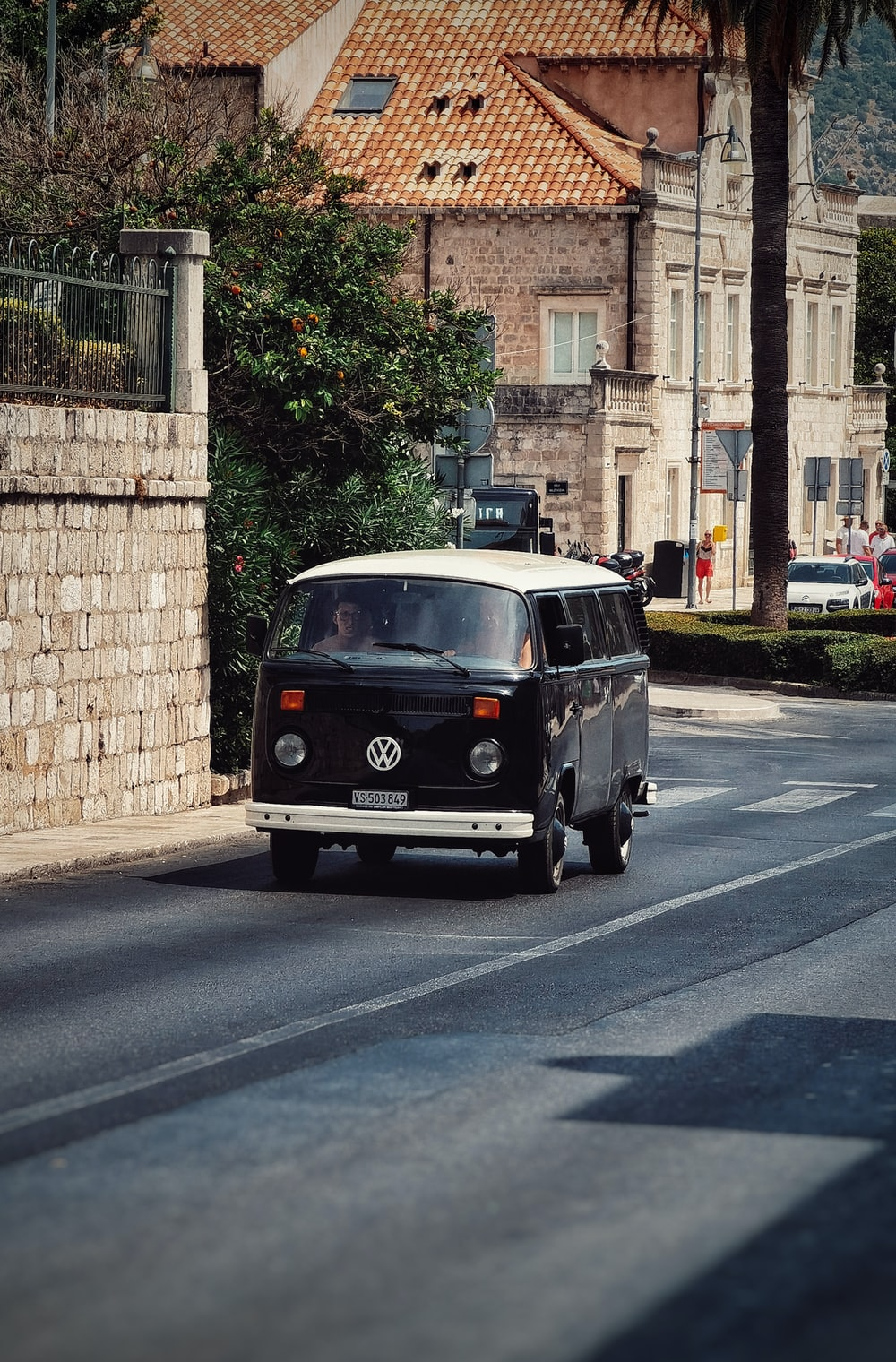 black and white volkswagen t-2 parked beside brown brick building during daytime