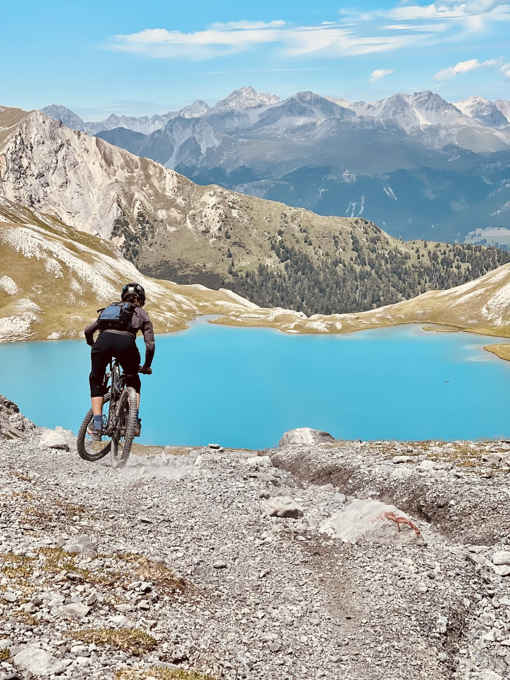 man in black jacket riding bicycle on mountain during daytime