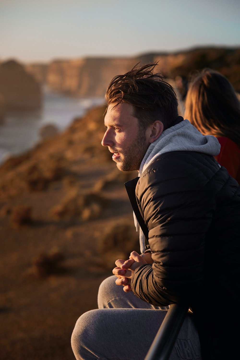man in black jacket holding woman in red shirt near body of water during daytime