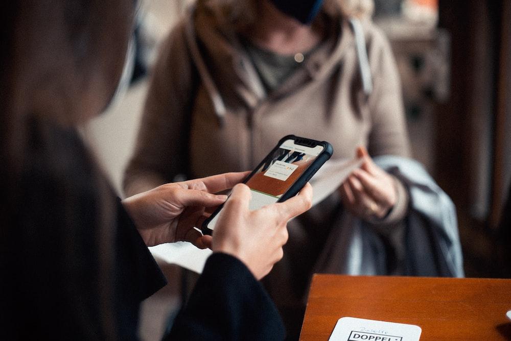 woman in brown coat holding black smartphone