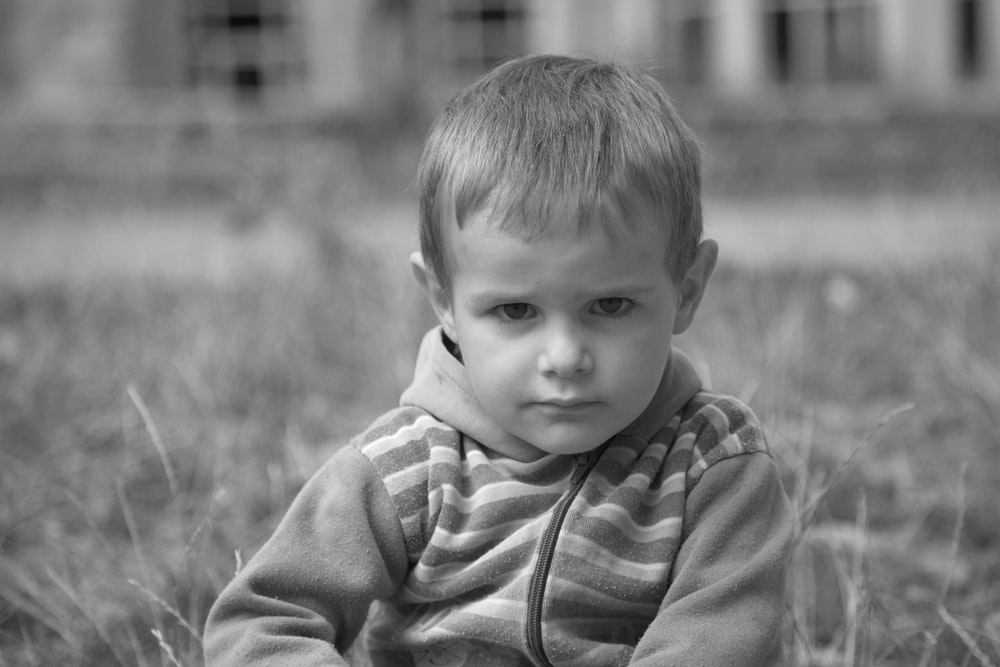 grayscale photo of boy in striped shirt