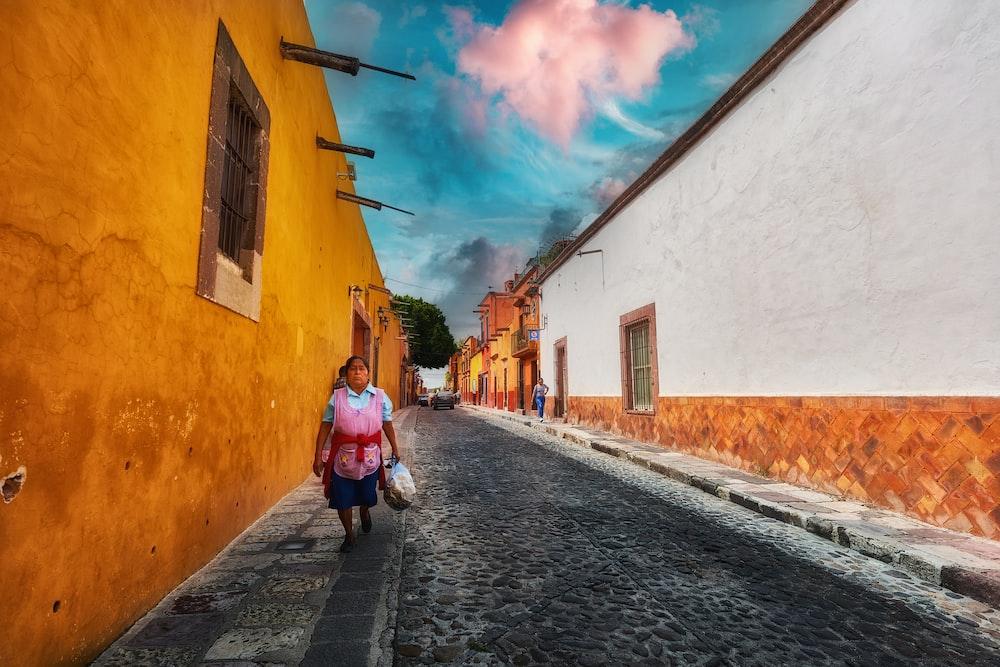 woman in pink jacket walking on street during daytime