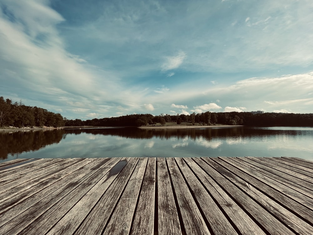 brown wooden dock on lake under blue sky during daytime