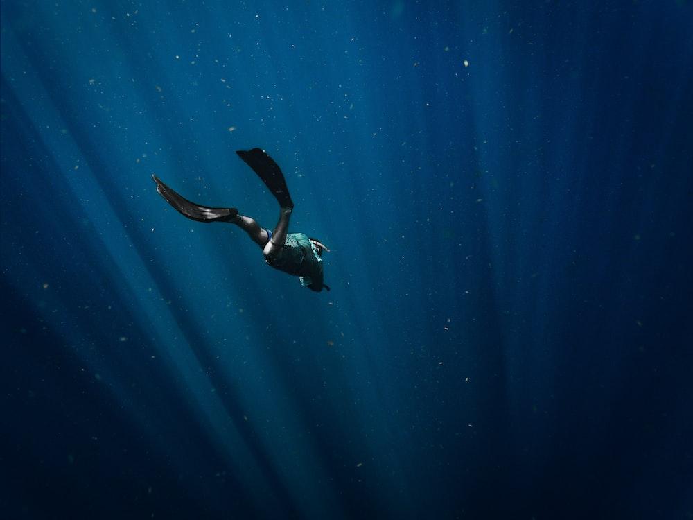 man in black wetsuit swimming in blue water