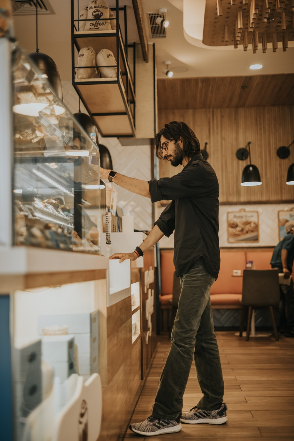 man in black long sleeve shirt and gray pants standing beside glass display counter
