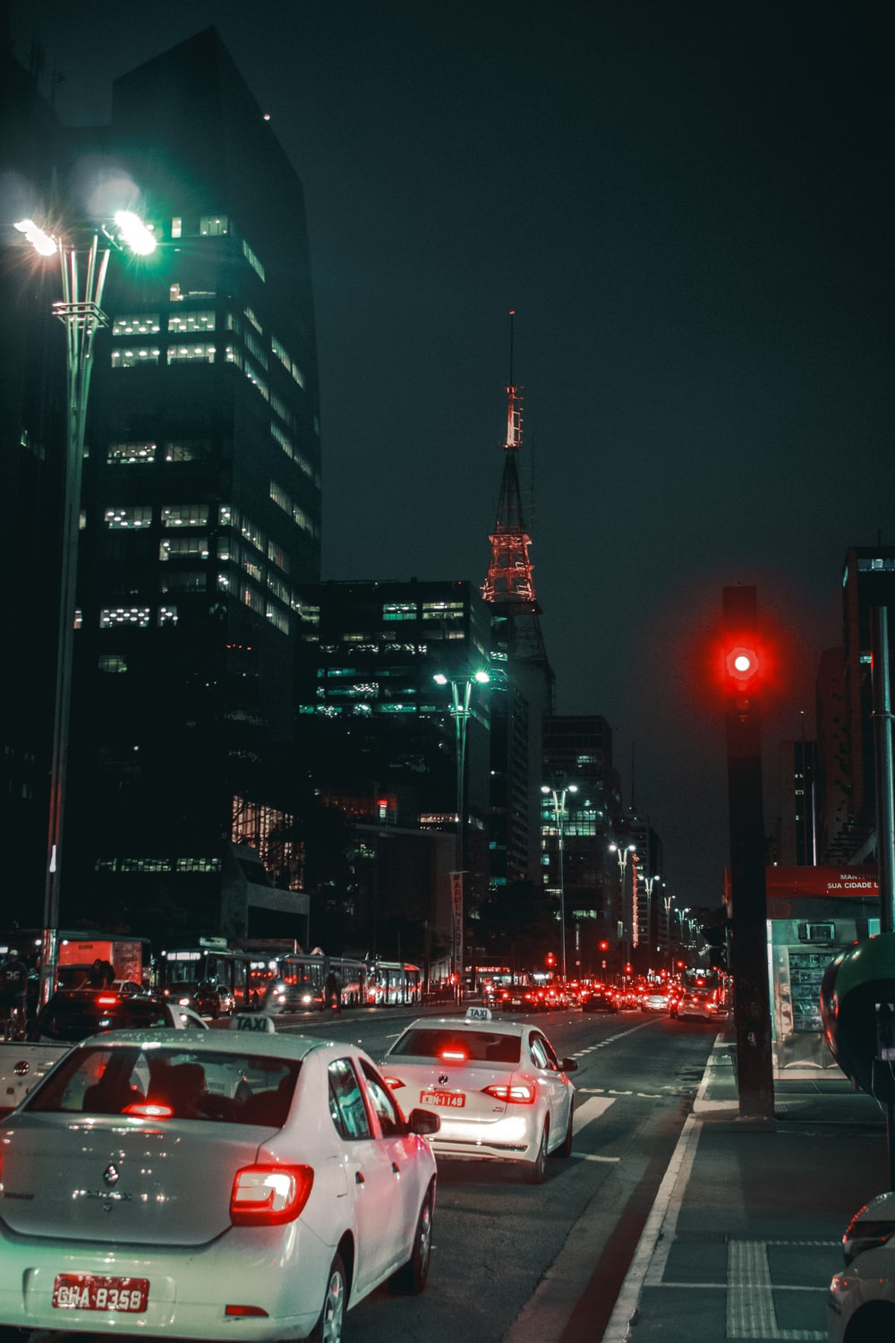 cars on road near high rise buildings during nighttime
