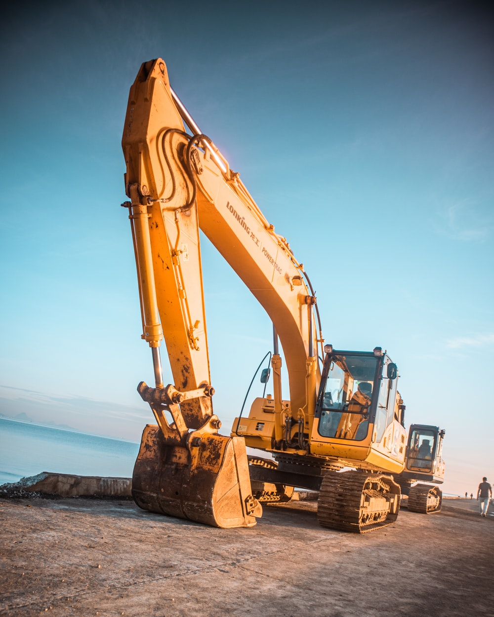 yellow excavator on gray rock near body of water during daytime