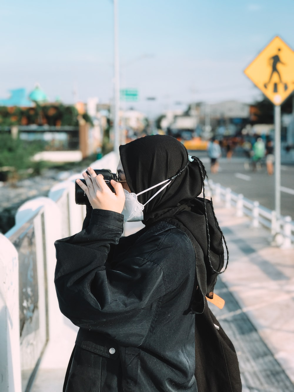 person in black hoodie using smartphone during daytime