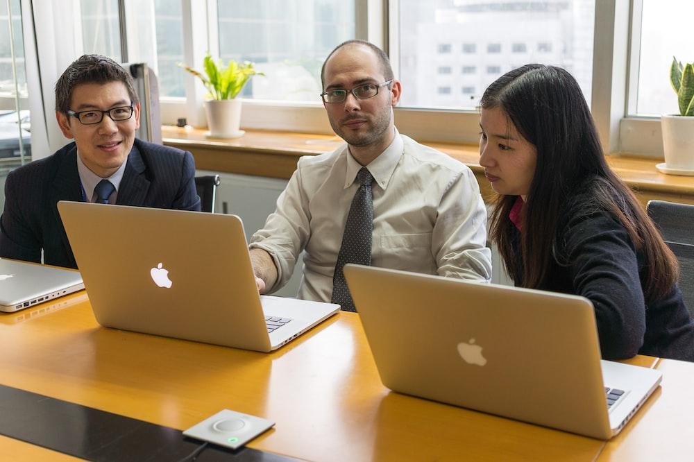man in white dress shirt sitting beside woman in black blazer using macbook