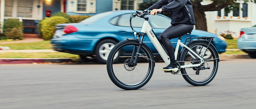 person in black jacket riding on blue bicycle during daytime