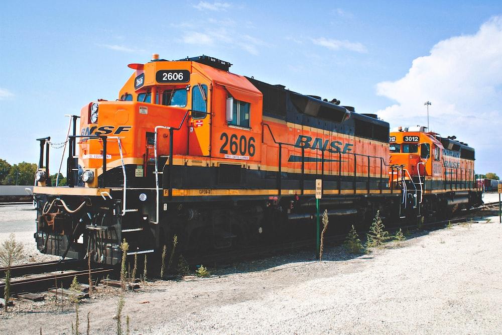 orange train on rail tracks during daytime