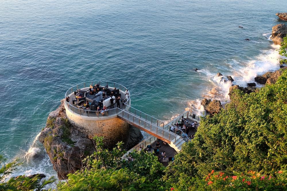 people walking on gray concrete bridge over blue sea during daytime