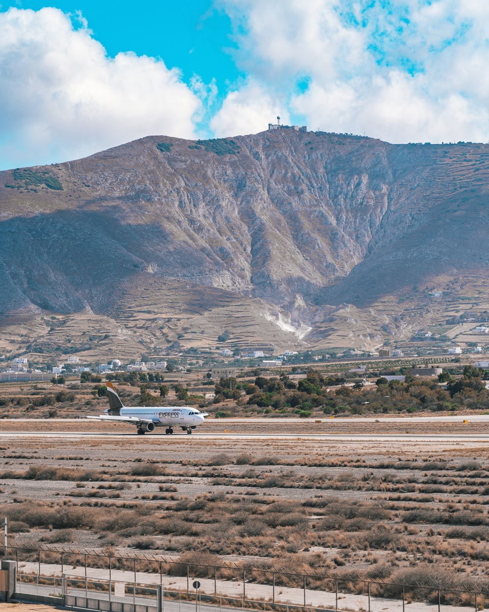 white airplane on brown field near mountain during daytime