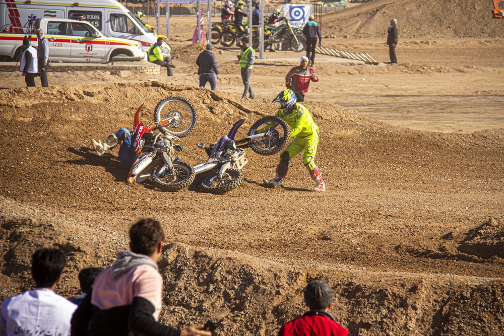 girl in red jacket and green pants riding motocross dirt bike