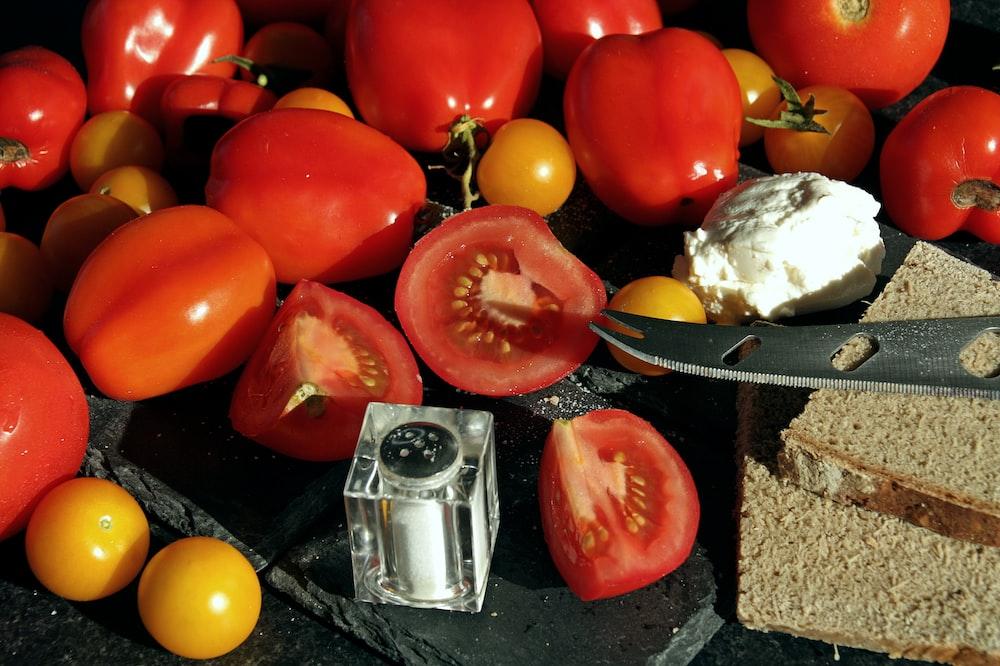 red tomato beside yellow round fruit