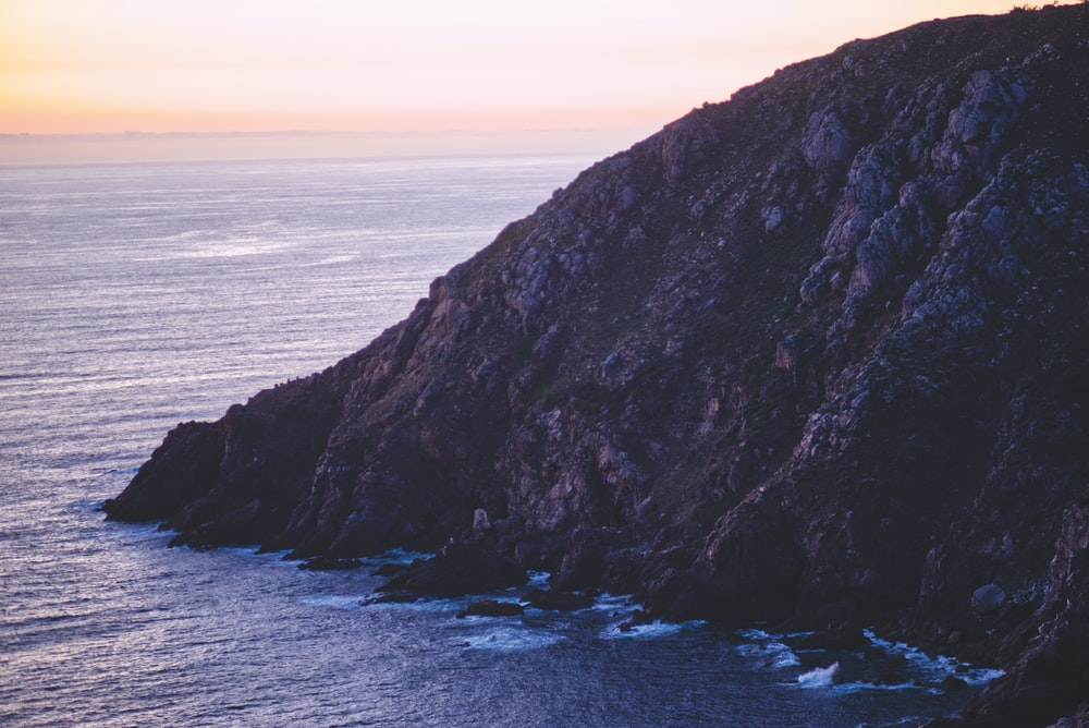 brown rocky mountain beside sea during sunset