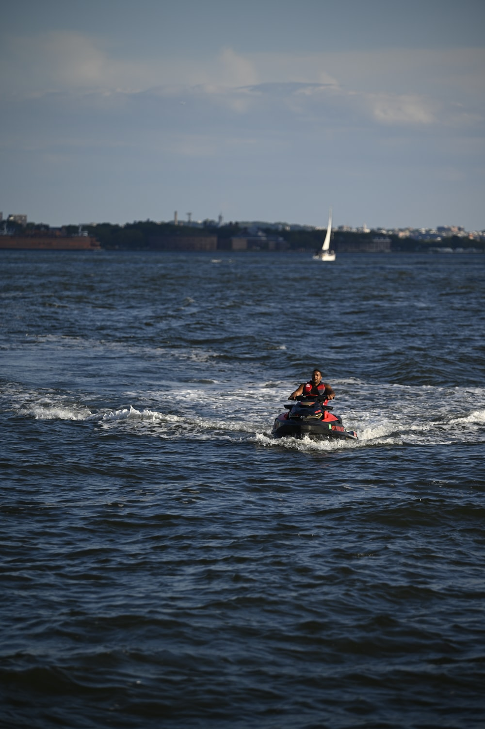 man in red and black vest riding on red kayak on sea during daytime