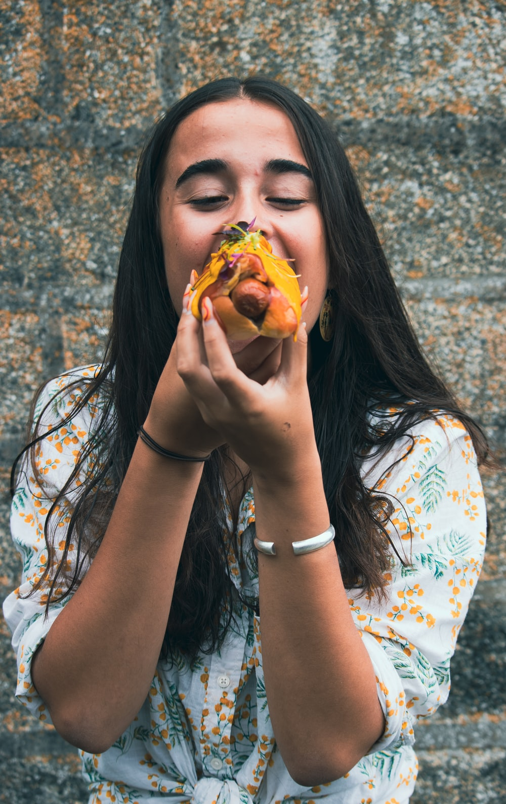 woman in white blue and red floral shirt holding a burger