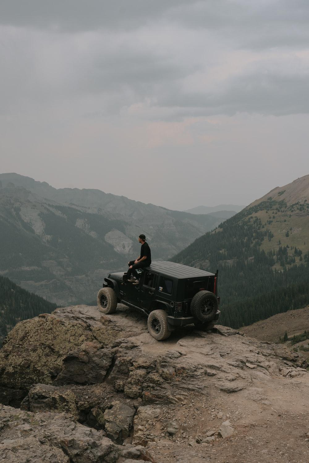 man in black shirt sitting on black jeep wrangler on rocky mountain during daytime