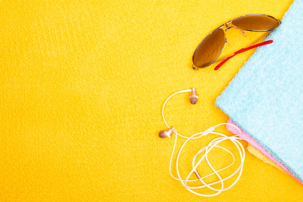 white earbuds on yellow textile
