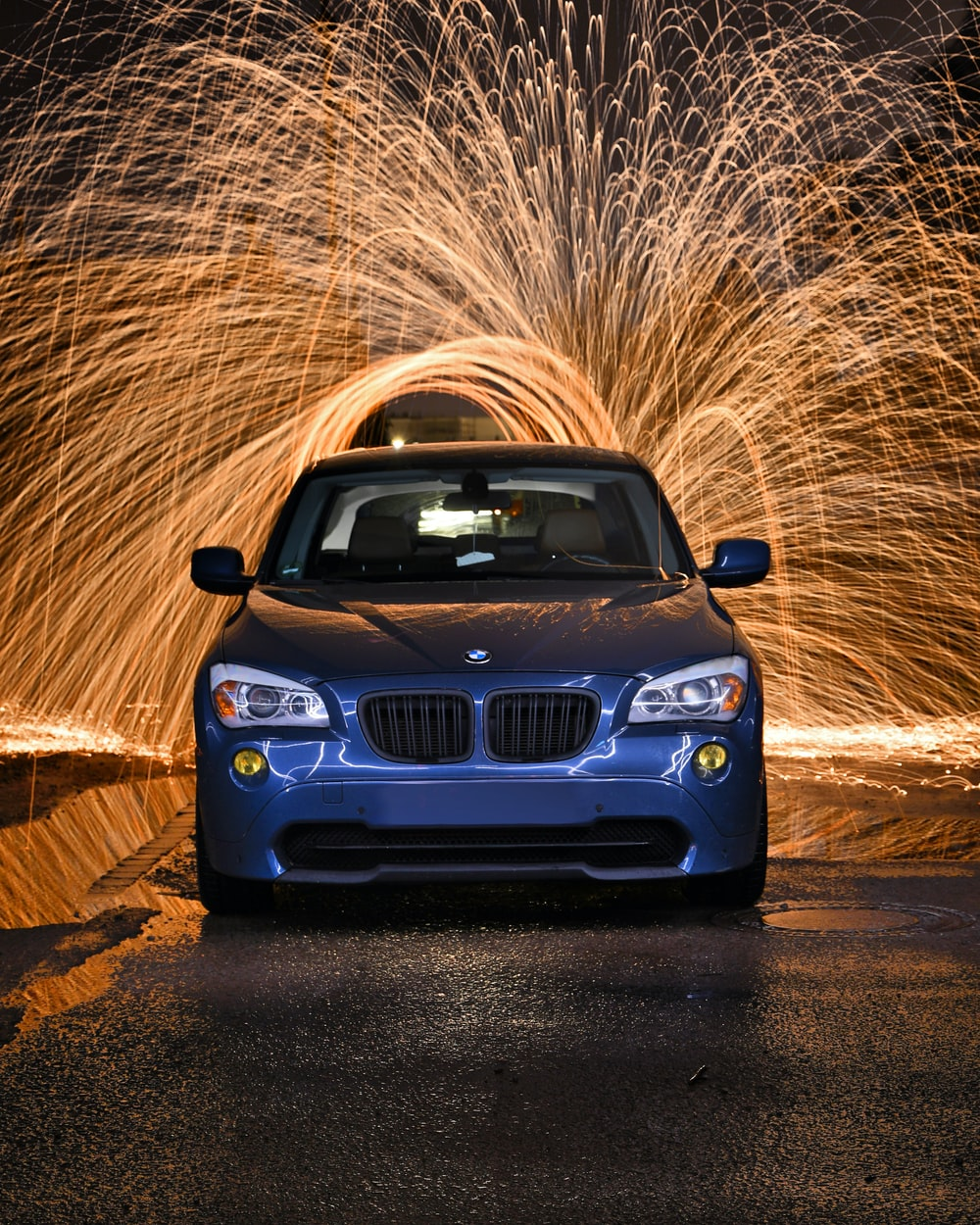 blue bmw car on brown dirt road during daytime
