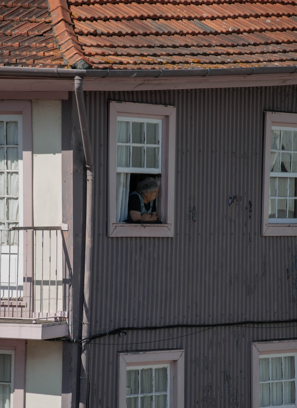 woman in black shirt standing in front of white wooden window