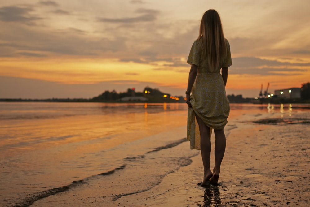 woman in brown dress standing on beach during sunset