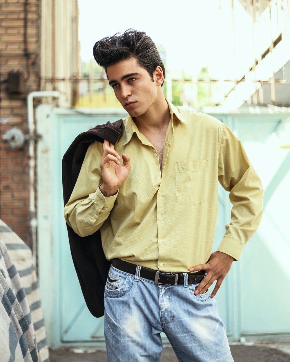 man in yellow dress shirt and blue denim jeans