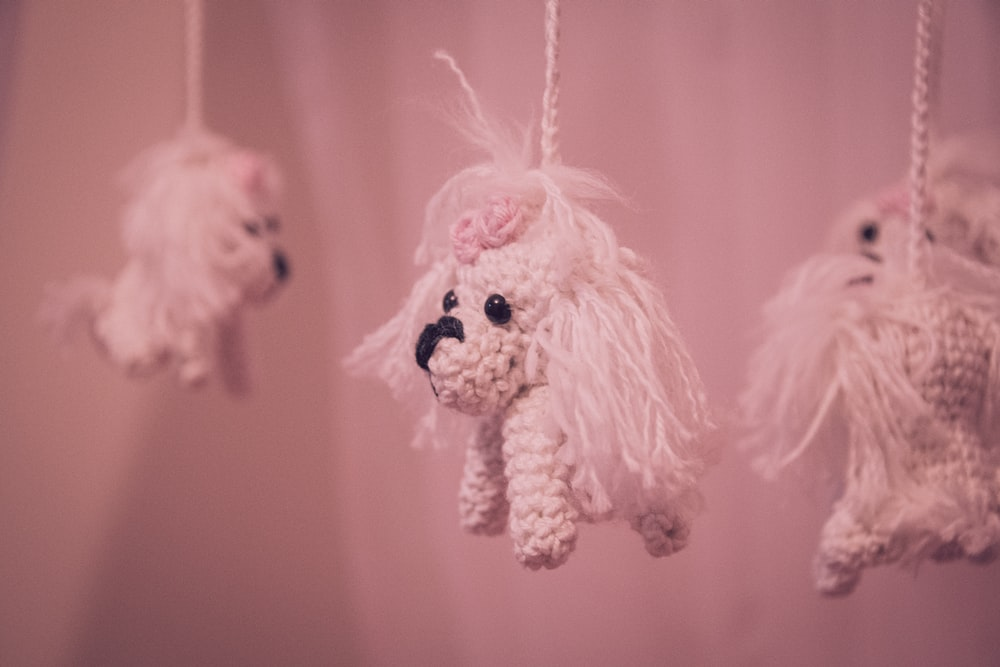 white dog plush toy on pink textile