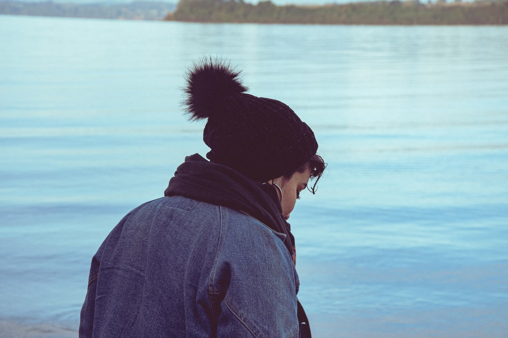 person in gray hoodie standing near body of water during daytime