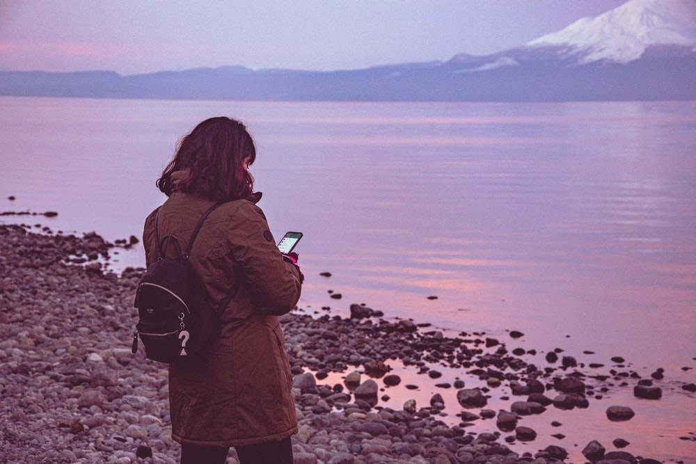woman in brown jacket standing on rocky shore during daytime