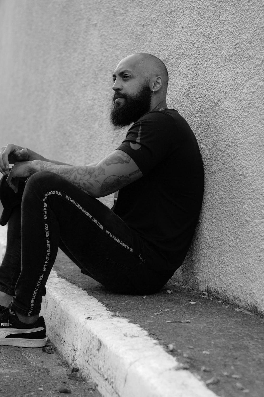 man in black long sleeve shirt and black denim jeans sitting on concrete floor
