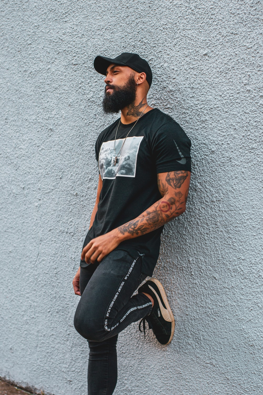 man in black crew neck t-shirt and black denim jeans sitting on concrete wall