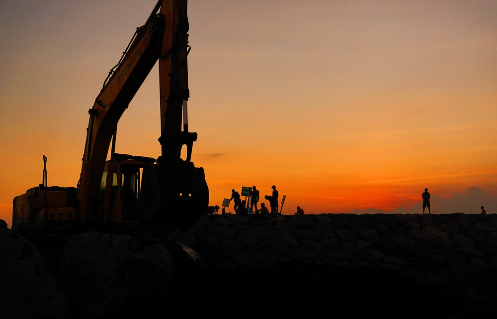 silhouette of people standing near excavator during sunset