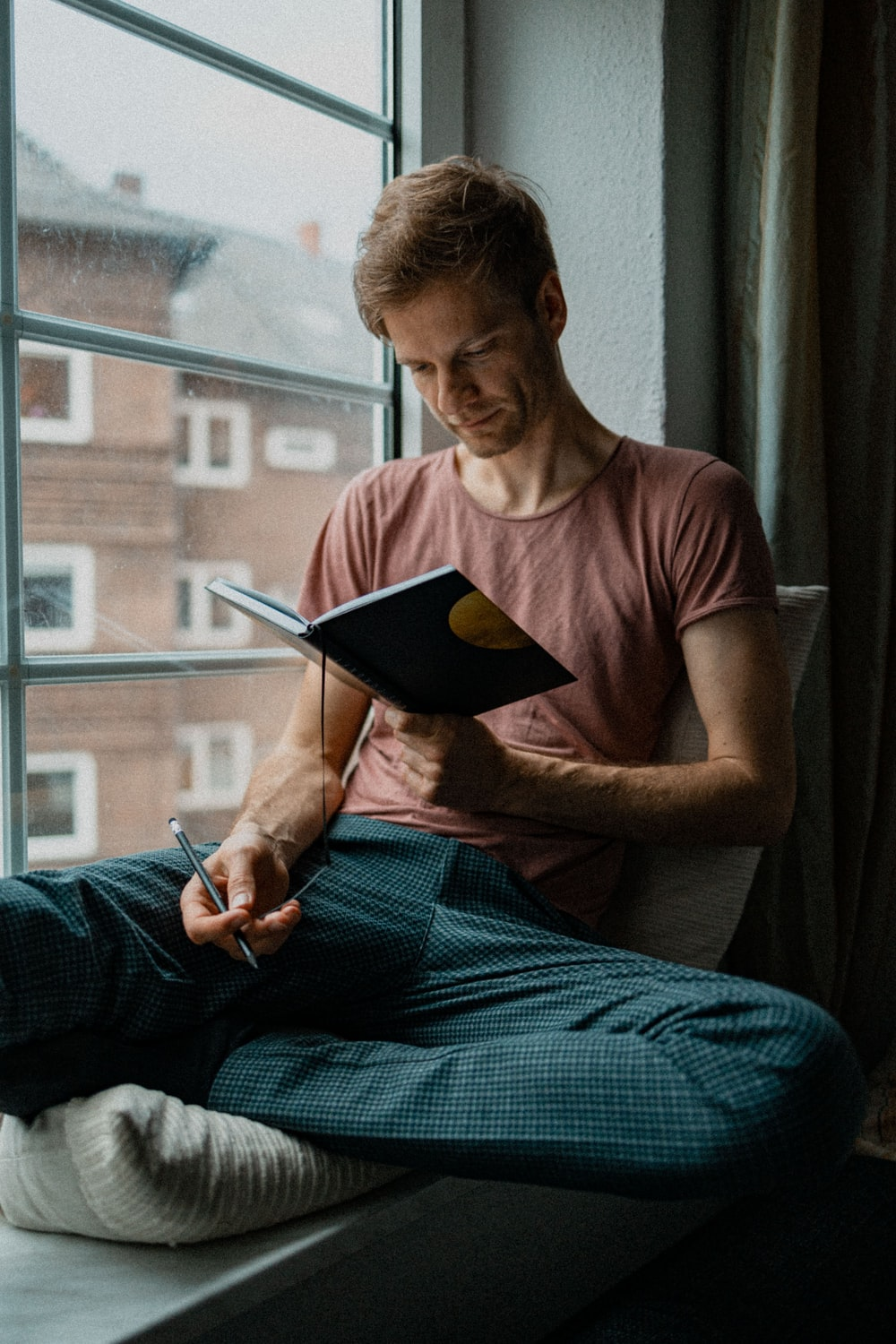 man in blue tank top holding book