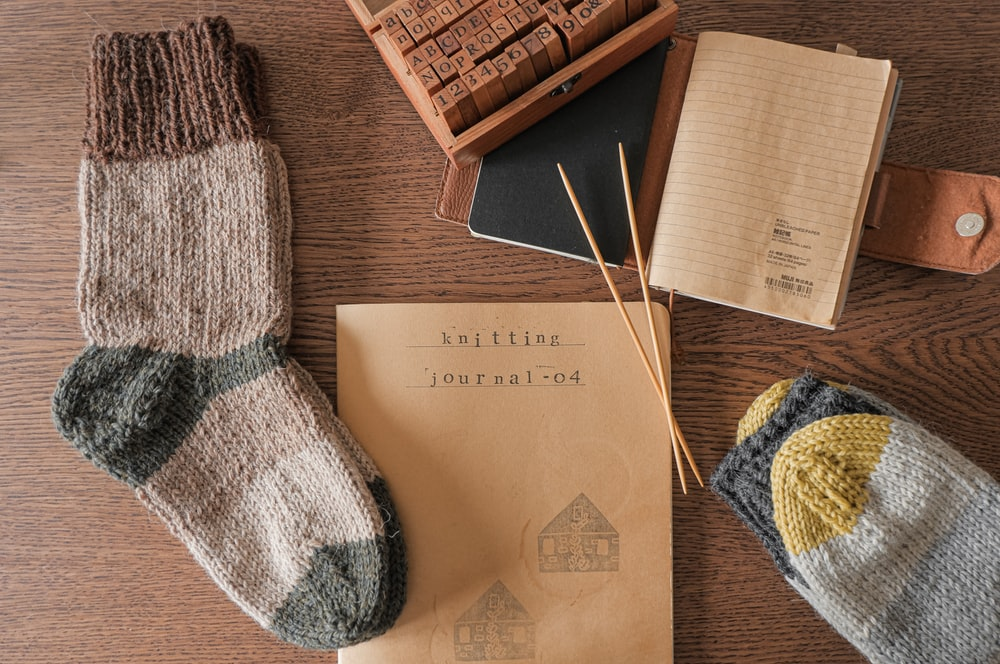 white and blue knit sock beside brown wooden box