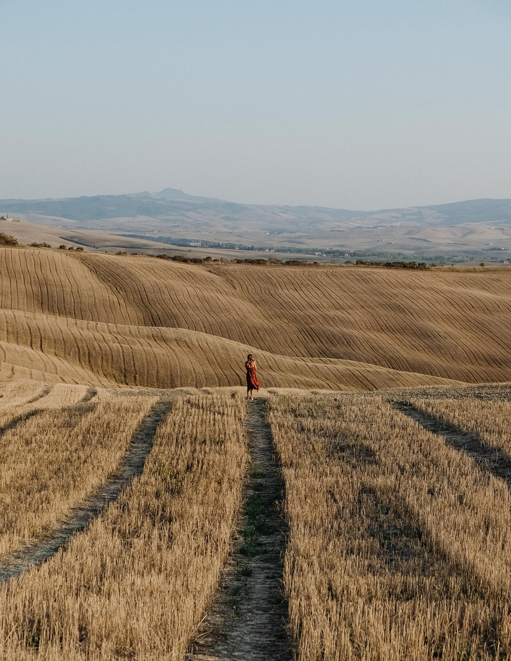 person in red jacket walking on brown field during daytime