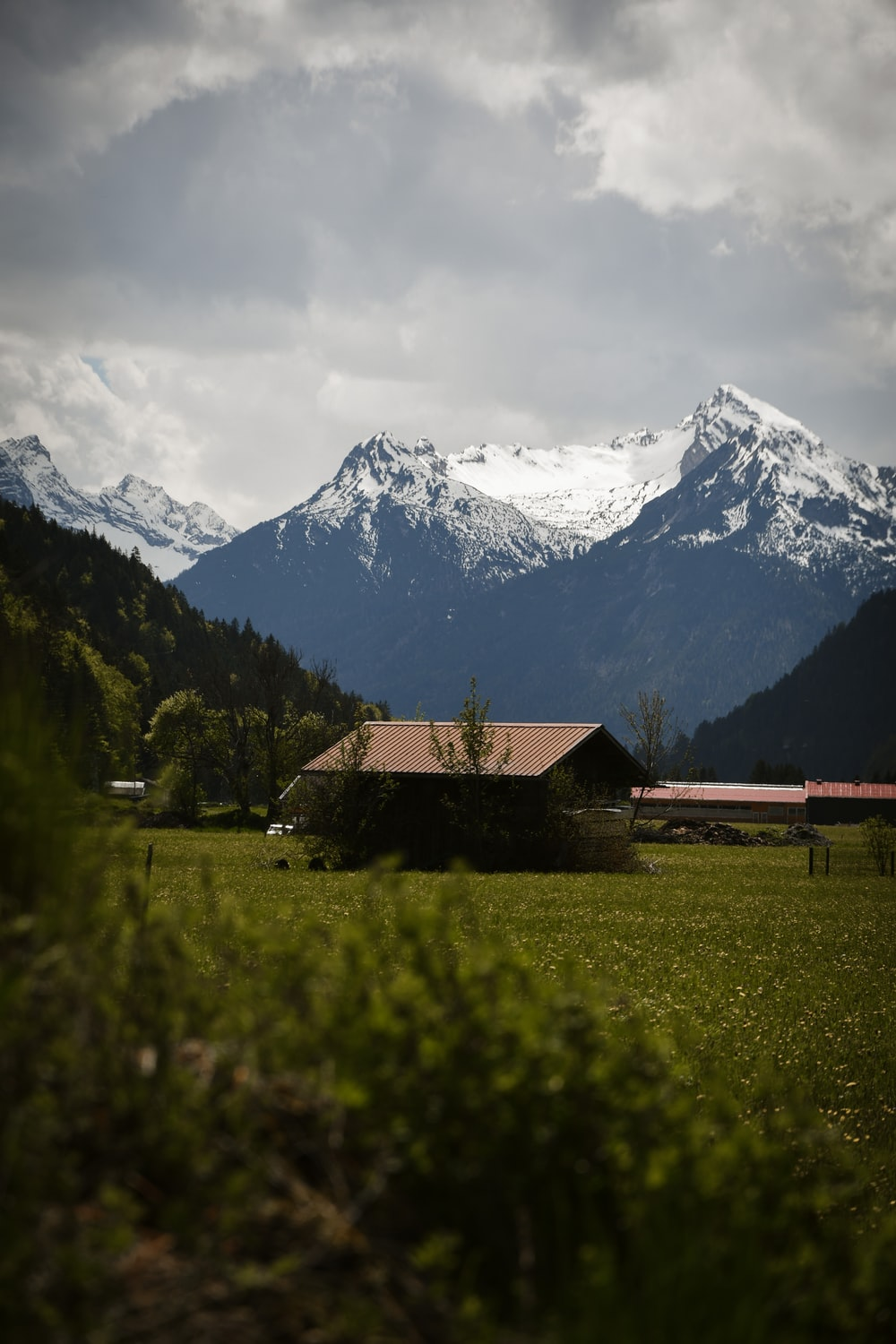 brown wooden house on green grass field near snow covered mountain during daytime